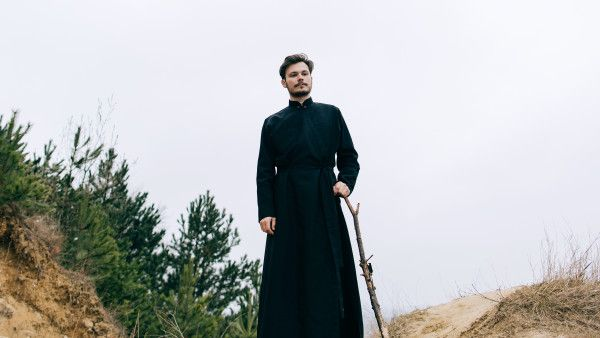 Portrait of handsome catholic bearded man priest or pastor posing outdoors in mountains