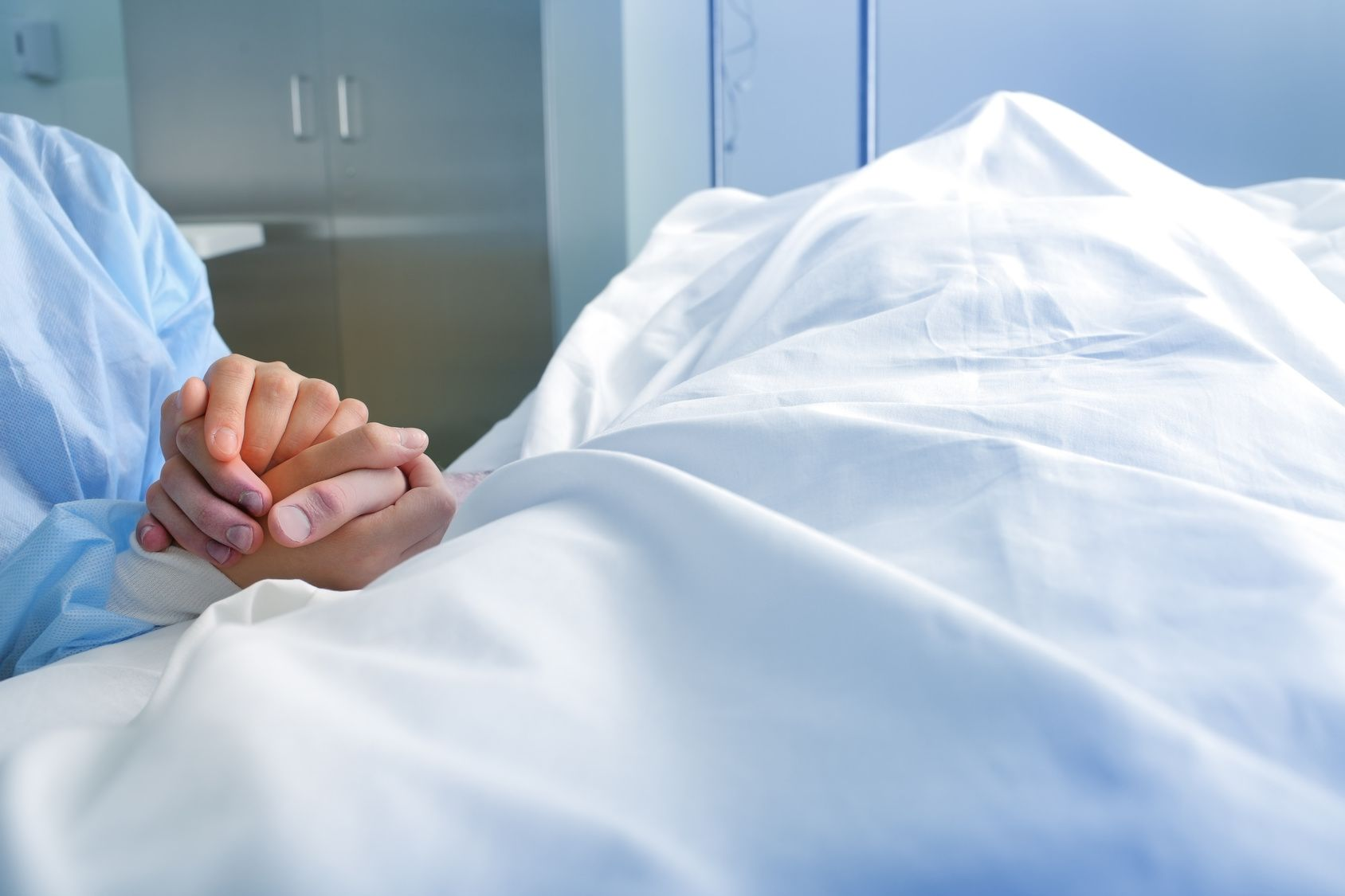 Wife holds the hand of the deceased spouse in the hospital