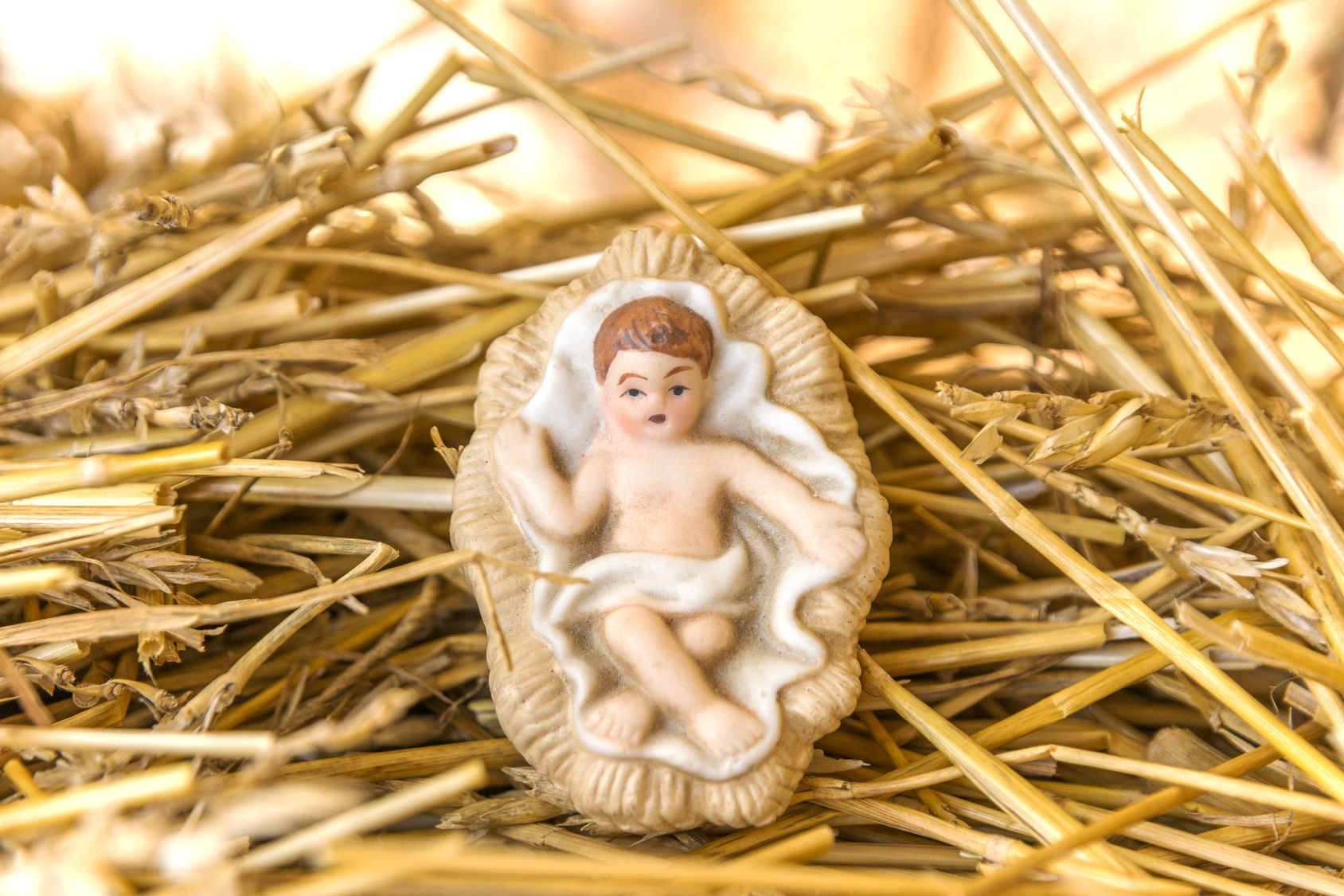Infant Jesus nativity decoration on a bed of straw against glowi