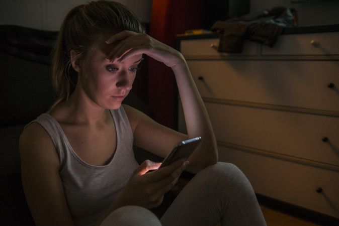 Sad and grumpy teenage girl sending message on her smart mobile
